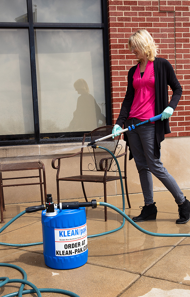 Woman disinfecting an outdoor seating area