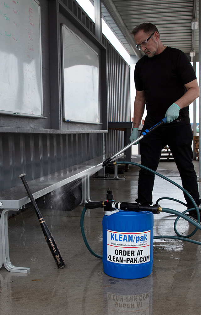 Man disinfecting bleachers in a baseball dugout
